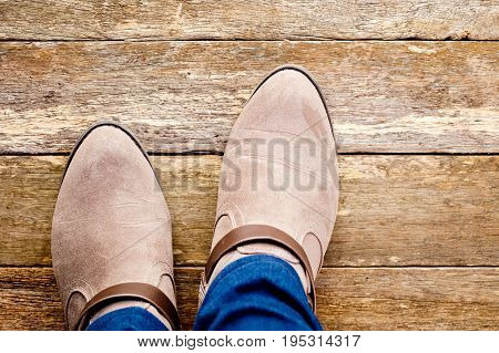 Women's suede styled country and western boots on rustic wooden background