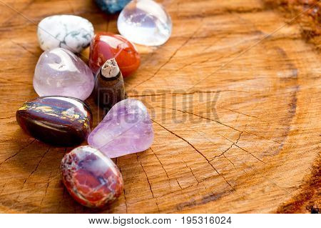 Burning Incense Cone With Tumbled Crystal Stones On Cross Section Of Timber Tree Log
