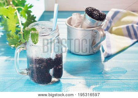Cold fresh lemonade with blackberry and mint in glass mason jar. Refreshing blackberry ice cold cocktail on blue table berries and ice for cocktail preparation. Tasty blackberry drink mojito.