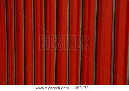 Texture of an old red iron wall with long bars