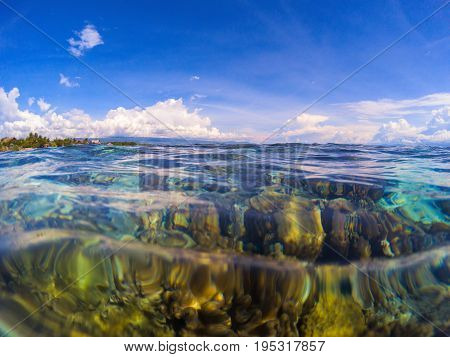 Double landscape with transparent water and sky. Transparent seawater with coral reef under water. Marine landscape with sea and sky. Clean sea water with ripples. Sunny day on tropical seashore