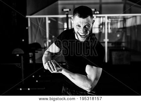 Screaming young man dressed in black t-shirt showing his biceps in gym. Man posing in gym and looking at camera while showing his biceps