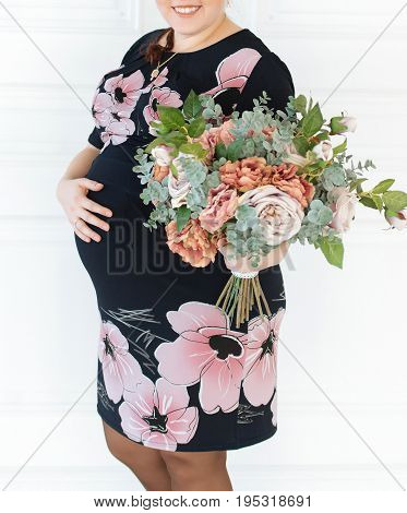 Young pregnant woman in dress with floral pattern touching her belly with hands on white background. Pregnant woman with bouquet of flowers in hand hugging her tummy
