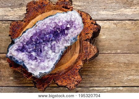 Amethyst Crystal Geode On Cross Section Of Timber Log With Wooden Plank Background