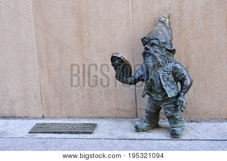 WROCLAW POLAND - JUNE 2017: Wroclaw a miniature statue of a gnome near the beauty salon. A dwarf with a mirror.