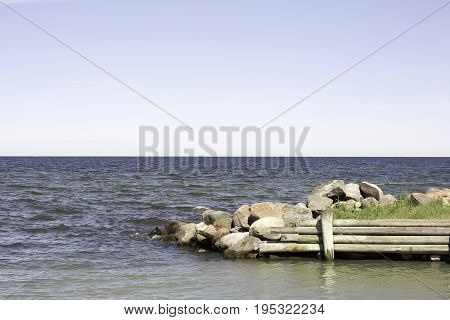 Breakwater with Ocean and a partly cloudy sky.