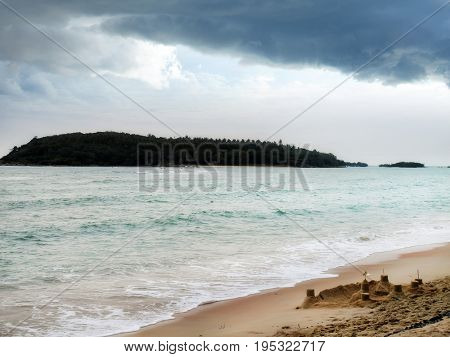 seascape image of beach with island view over sunny sky