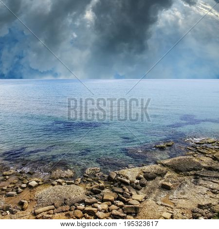 seascape image of rocky beach over stormy sky