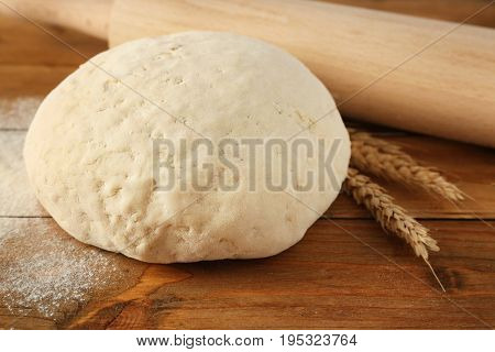 Ball of raw dough, wheat and rolling pin on wooden background