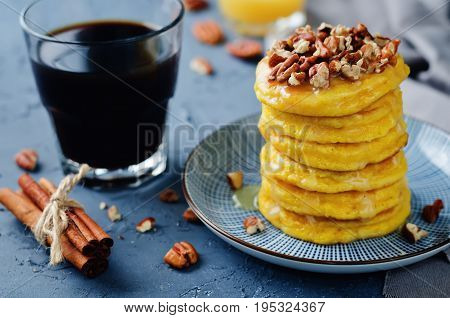 Pumpkin pancakes with pecans on a stone background