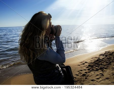 young adult woman taking picture on sandy beach
