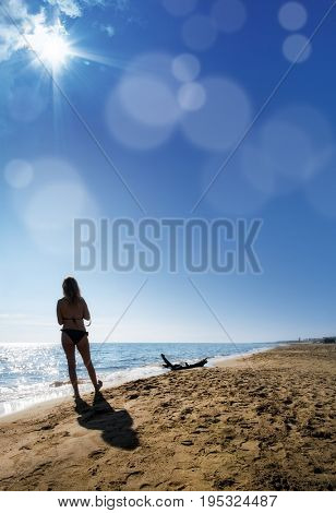 close up young adult woman walking on sandy beach