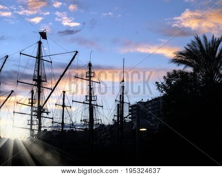sailing boats silhouetted by sunset light in harbor of Antalya