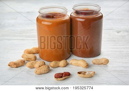 Jars with creamy peanut butter on table