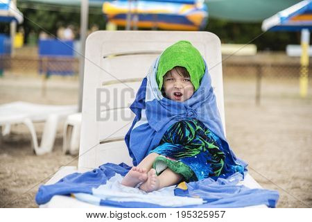 The little girl wrapped in towels for warming emotions of the face