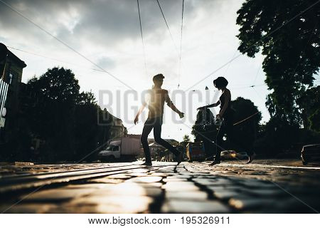 boy and girl run across the street holding hands