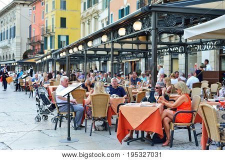 VERONA ITALY - MAY 2017: Summer terrace of the restaurant in the center of Verona near the arena. People are eating dinner. Rest of tourists.