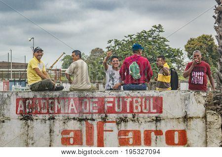 GUAYAS, ECUADOR, OCTOBER - 2016 - Group of adult men over a wall saying hello to the camera at Guayas district Ecuador