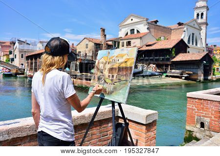 VENICE ITALY - MAY 2017: A woman paints with oil on canvas the view of the gondolas workshop in Venice.