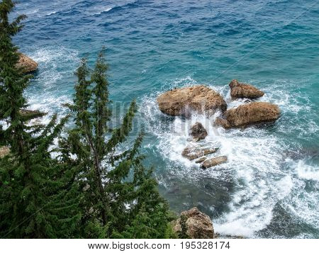 elevated view of rocks in blue water sea and waves in Antalya, Turkey