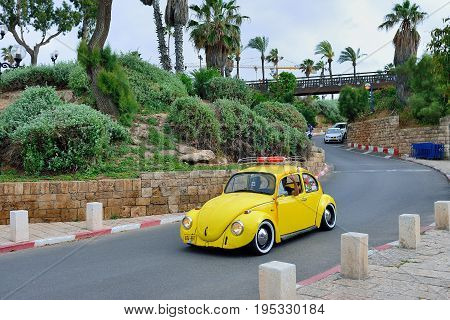 TEL AVIV ISRAEL - APRIL 2017: A company of young people on an old yellow Volkswagen the old town of Jaffa Tel Aviv