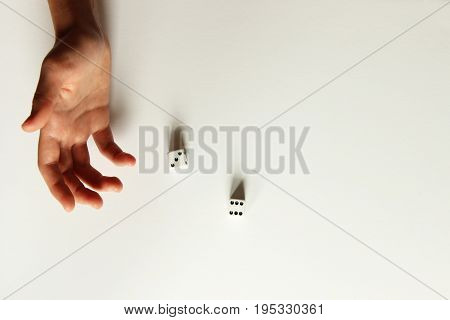 One human hand releasing two dice onto white background with copy space.