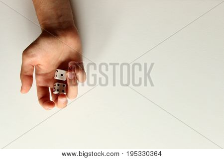 One female hand holding two dice. White copy space background.