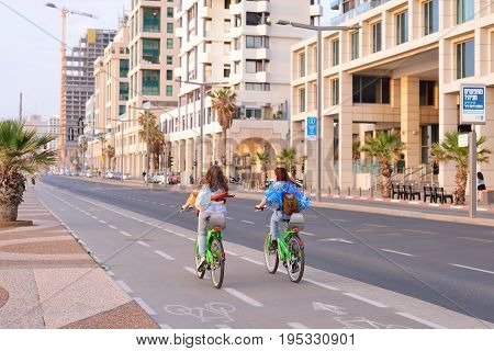 TEL AVIV ISRAEL- APRIL 2017: Herbert Samuel st. bike track and walking area for pedestrians in the center of Tel Aviv. Girls ride bicycles on holiday