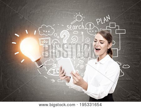 Happy blond businesswoman looking at her tablet screen and screaming with joy. Blackboard with a shining light bulb and a business scheme drawn on it.