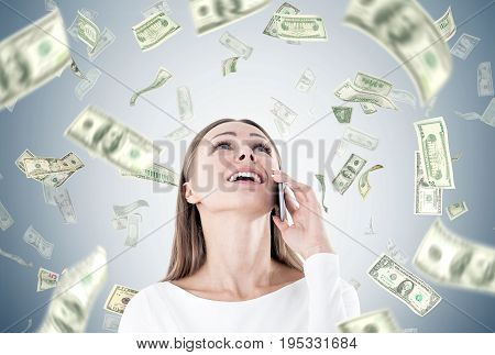 Portrait of a happy young and beautiful businesswoman talking on a smartphone and looking upwards. Gray wall with dollar bills falling around