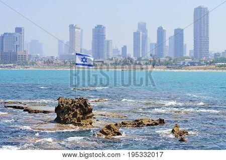 TEL AVIV ISRAEL - APRIL 2017: The flag of Israel against the background of modern Tel Aviv the Mediterranean Sea.