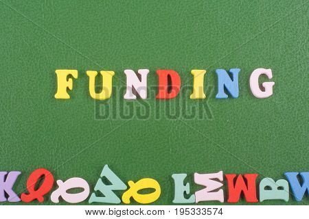 FUNDING word on green background composed from colorful abc alphabet block wooden letters, copy space for ad text. Learning english concept