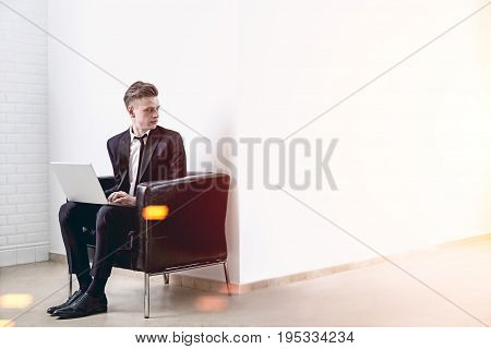 Blond businessman is sitting with his laptop in a leather armchair near a white wall in an empty room or office. Toned image mock up