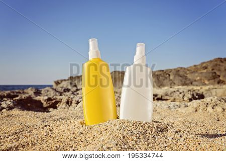 Two bottles of the product for sunbathing and after on a sandy background. Summer skin care concept