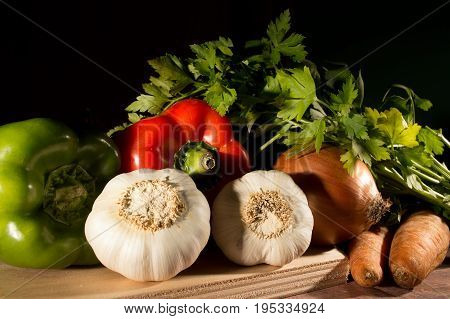 garlic peppers onion carrots and parsley grouped and ready to cook on black background