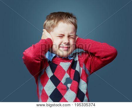 unhappy boy closing ears, isolated against grey