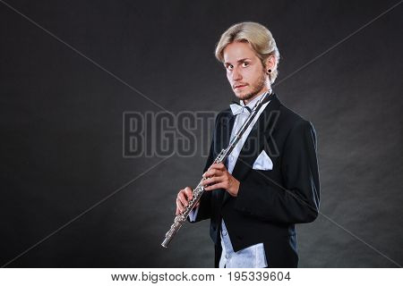 Classical music passion and hobby concept. Portrait of elegantly dressed musician blonde young man holding flute. Studio shot on dark grey background