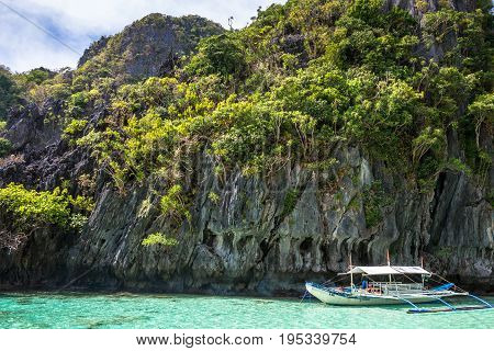 EL NIDO PALAWAN PHILIPPINES - JANUARY 17 2017: Vertical picture of sharp rocks with blue sky in El Nido Bay during island hopping.