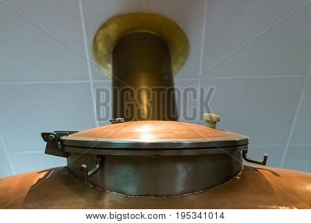 copper hatch on a large tank on the background of a pipe leaving the white ceiling