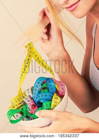 Diet healthy eating weight loss and slim body concept. Fit fitness girl holding bowl with many colorful measuring tapes