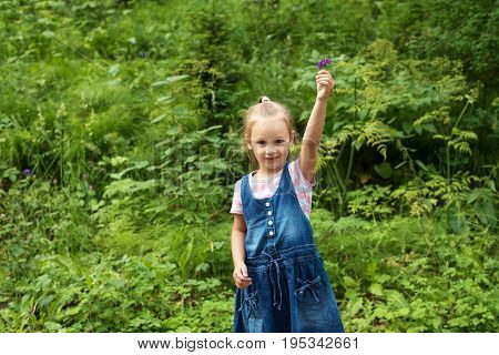 Little girl in a demin dress with a wildflower in the summer Siberian forest.