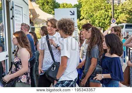 PARIS, FRANCE - JUNE 24, 2017: Unknown young people standing in line for control to get into the territory of the Eiffel Tower.