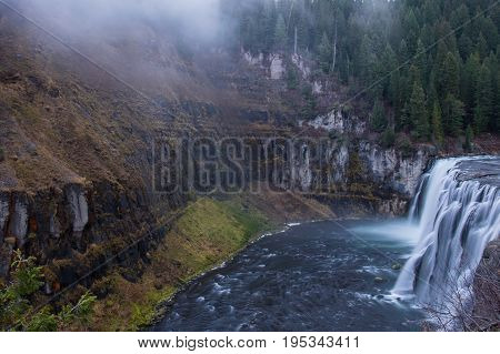 Waterfall at Mesa Falls with fog coming up from the water near dusk.