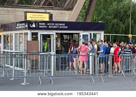 PARIS, FRANCE - JUNE 24, 2017: Unknown people standing in line for control to get into the territory of the Eiffel Tower.