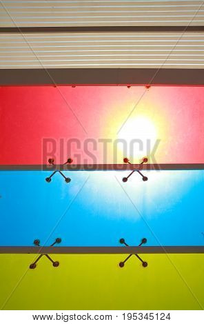 The sun is shining at red green yellow blue purple color glass windows of background