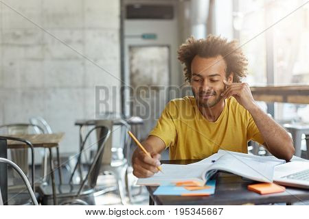 Creative Young Author With Curly Hair And Dark Skin Dressed Casually Sitting At Cafeteria Preparing