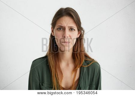 Sad Young Woman With Long Dark Hair, Charming Eyes And Pure Skin Curving Her Lips Looking With Disap