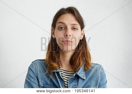 Waist Up Portrait Of Pretty Young Female Raising Her Eyebrow With Wonder Dressed In Denim Jacket Iso