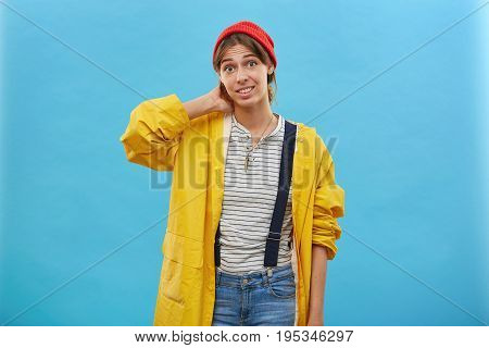Indoor Shot Young Female In Yellow Loose Jacket, Denim Overalls And Red Hat Keeping Her Hand On Neck