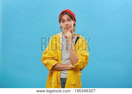 Portrait Of Pretty Female Dressed In Yellow Raincoat And Red Hat Keeping Her Hand On Chin Looking Di